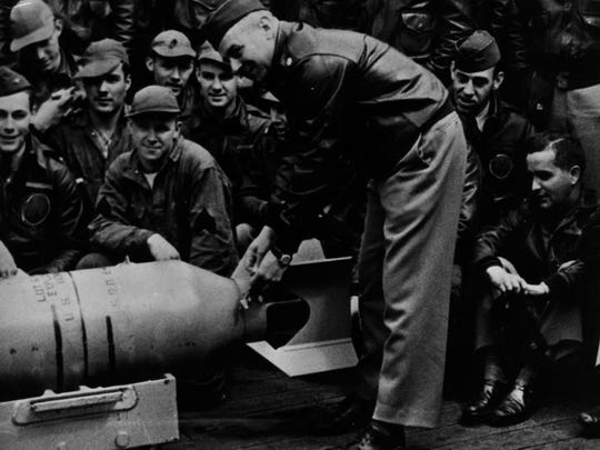 """LT. Col. James Doolittle wires a Japanese medal to the fin of a 500-pound bomb aboard the USS Hornet prior to the Tokyo raid in 1942. From the Enquirer archives scanned July 6, 2011 FROM AN APRIL 4, 1967 ARTICLE BY KIP COOPER, COPLEY NEWS SERVICE: Tokyo - Tora! Tora! (tiger, tiger) was the Japanese signal launching the infamous sneak attack on Pearl Harbor. Four months later, on April 18, 1972, 80 gallant U.S. Army Air Corps men carrying two pints of """"medicinal rye"""" in their hip pockets, a bomb inscribed """"I don't want to set the world on fire, just Tokyo"""" and other assorted missives, were winging their way into the """"tiger's"""" very lair to do just that. Jimmy Doolittle's 16 B25s had been brought by stealth and daring right into the tiger's den by that intrepid U.S. admiral, William F. """"Bull"""" Halsey, personally selected for the dangerous mission of helping avenge Pearl Harbor by the World War II naval genius, the late Fleet Adm. Chester W. Nimitz. Doolittle's raid hit Tokyo, Yokohama, Kobe, Osaka, Nagoya and Yokosuka. Seaman Suekichi Nakamura, the lookout on a Japanese patrol boat some 700 miles from his own shores, spied two aircraft carriers on the horizon. He awakened his sleeping skipper, Chief Petty Officer Gisaku Maeda, to admire """"our beautiful carriers."""" Maeda studied the carriers intently, then said sadly, """"Indeed, they are beautiful. But they are not ours."""" He then shot himself. He knew what the appearance of USS Hornet and Enterprise portended. In Yokohama, European and American residents had been interned in the port city's famous Negishi Heights racetrack grandstand in the """"Banzai (hurrah) Room"""" where Japanese bettors used to toast their winnings. """"We has something to really 'banzai' about that day,"""" recalls Britisher Hugh Walker, 57, who lives here today (1967) with his Japanese wife and five children. """"I was outside when I saw the planes coming in very, very low,"""" Walker said in an interview. """"We climbed the fence to watch them go over. A Greek sailor tol"""