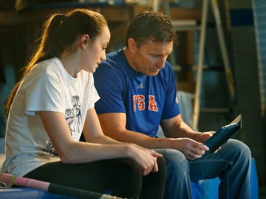 Gates Chili freshman Erica Ellis and Coach Rick Suhr look at video of a jump while training at the Suhr's home facility in Churchville in early January 2016.