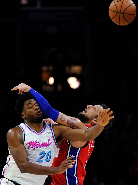 Miami Heat's Justise Winslow (20) and Philadelphia 76ers' Marco Belinelli (18) collide while reaching for a loose ball in the first half of an NBA basketball game, Wednesday, Feb. 14, 2018, in Philadelphia. (AP Photo/Michael Perez)