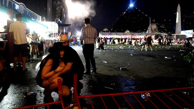 People take cover at the Route 91 Harvest country music festival after apparent gun fire was heard on October 1, 2017 in Las Vegas, Nevada.  There are reports of an active shooter around the Mandalay Bay Resort and Casino.