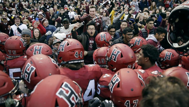 Harvard players, students and fans celebrate their 45-27 win over Yale at Fenway Park in 2018. The Ivy League has canceled all fall sports because of the coronavirus pandemic.
