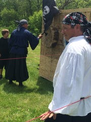 With the help of Jeff Seward, right, and Chad Piper, left, those at the Iowa Renaissance Festival were able to learn the art of ax throwing Saturday.