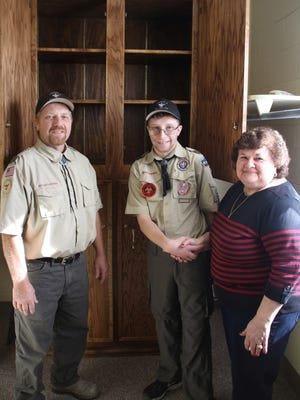 Jimmy Artis, a member of Boy Scouts of America Troop 4, is pictured at the Millville Woman's Club with his father, James Artis, leader, Boy Scouts of America Troop 4, and Carol Calareso, trustee, Millville Woman's Club. They are standing in front of a cabinet that Jimmy built during the summer, with assistance from his father, as part of his Eagle Scout project.