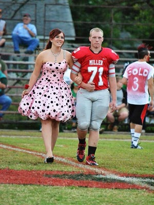 Jordan Berns (71) escorts a queen candidate at midfield during homecoming.