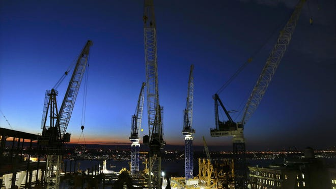Cranes move loads of materials at dusk at the Hudson Yards construction site in New York on March 4. The steel behemoths are sprouting up all over the city, a prime force in New York's building boom capped by a sea of skyscrapers that are changing the famed urban skyline.