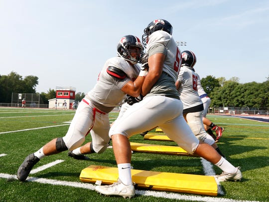 Chris Fowx, 57, right, works out on the new turf field during varsity football practice at RC Ketcham High School in Wappingers Falls on Tuesday, August 22, 2017.