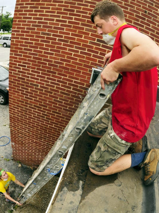 Stephen Ginder, 15, moves a laddar for Ariana Maas while they are refurbiishing Tuesday, June 16, 2015 at a Mainsville home. Ryden is a member Reach Workcamp, a group of teens from Mchigan and North Carolina who are in the state to make home repairs as a service project. Markell DeLoatch - Public Opinion