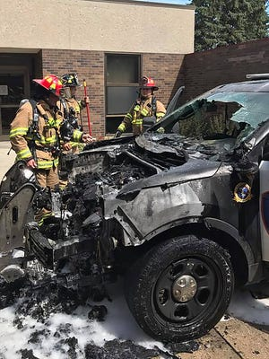 City of Fond du Lac Fire/Rescue personnel examine the aftermath of a City of Fond du Lac Police Department cruiser that had started on fire Thursday while parked at the Fond du Lac County Health Care Center  at 459 E. First St.