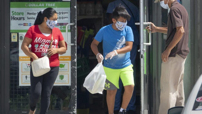 Customers wearing masks enter and leave the Dollar Tree on Okeechobee Boulevard in West Palm Beach Wednesday, June 24, 2020, after county commissioners voted unanimously Tuesday to require masks inside buildings open to the public.