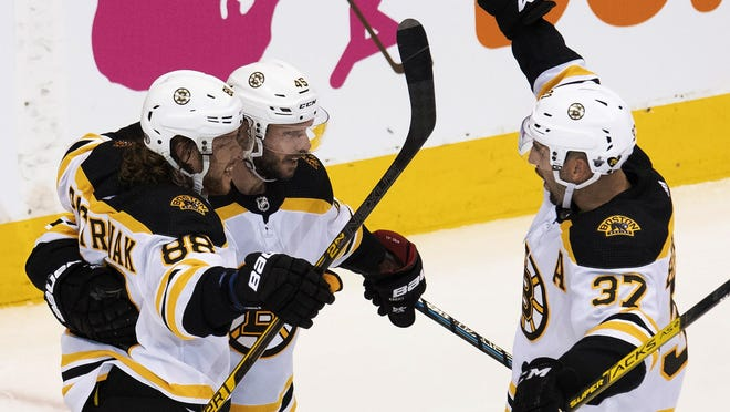 Boston right wing David Pastrnak (88) is congratulated by teammates center Patrice Bergeron (37) and center David Krejci (46) after scoring during the second period of Sunday's game in Toronto against Tampa Bay.