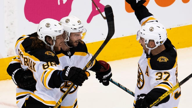 Bruins center Patrice Bergeron, right, joins the celebration after right wing David Pastrnak, left, scored in the second period against the Tampa Bay Lightning in Toronto on Sunday night in Game 1 of a second round best-of-seven series.