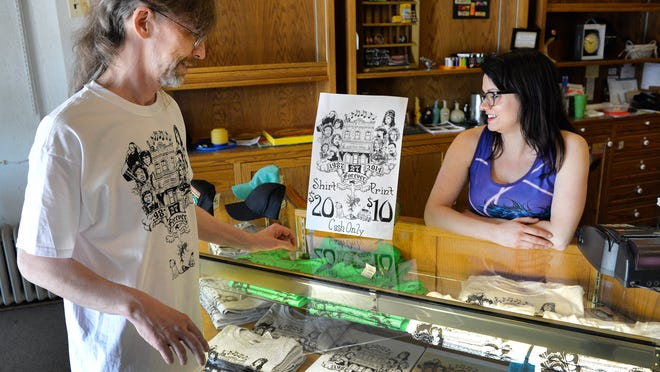 """Electric Fetus Clerk Andy Valenty and Assistant Manager Sarah Rieland look over the commemorative T-shirts designed by Valenty that are being sold. Their theme is """"27 Forever"""" after the business, which is closing after 27 years, and the musicians who also shared the fate of living just 27 years."""