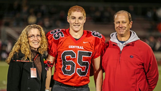 """Timothy Piazza, center, with his parents Evelyn Piazza, left, and James Piazza, right, during Hunterdon Central Regional High School football's """"Senior Night"""" at the high school's stadium in Flemington, N.J."""