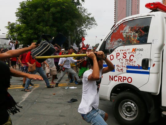Protesters hit a Philippine National Police van after