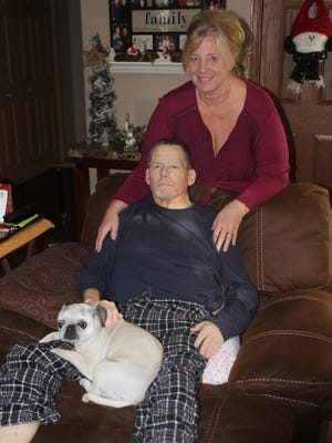 Garth (seated) and Della Cooney at the Marengo home. A benefit to help assist the couple is Saturday, Dec. 9, in Amana.