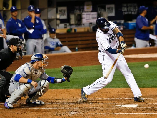 San Diego Padres' Matt Kemp hits a two-run single against the Los Angeles Dodgers during the second inning of a baseball game Thursday, Sept. 3, 2015, in San Diego. The Dodgers catcher is Yasmani Grandal and the umpire is Adam Hamari. (AP Photo/Lenny Ignelzi)