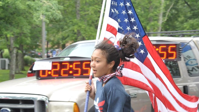 Breanna Murrin carried the flag the whole race at the annual Brevard Firecracker 5K last year. Thee Brevard Rotary Club sponsors the annual 5K, 10K and Fun Run on July 4.