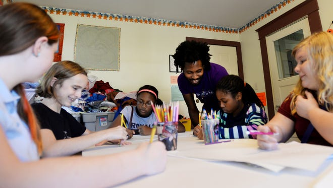Art teacher Jared Leeaux works with students at the Renzi Center Wednesday afternoon.