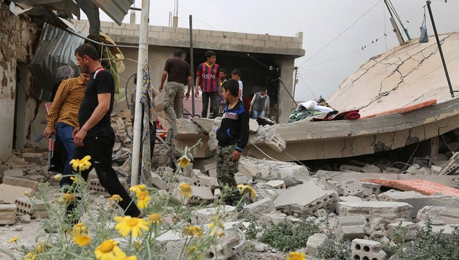 Syrians inspect the damage following clashes between Syrian pro-government fighters and Kurdish forces, in the northeastern city of Qamishli, on April 21, 2016.