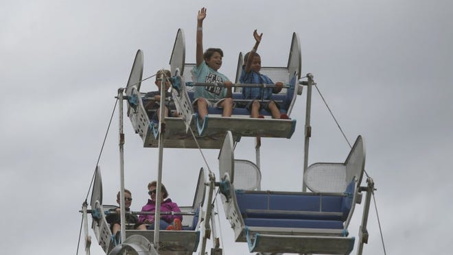 Kevin Garcia, 12, center left, and Cayden Urban, 9, wave to family members  during the Shasta District Fair in 2016.