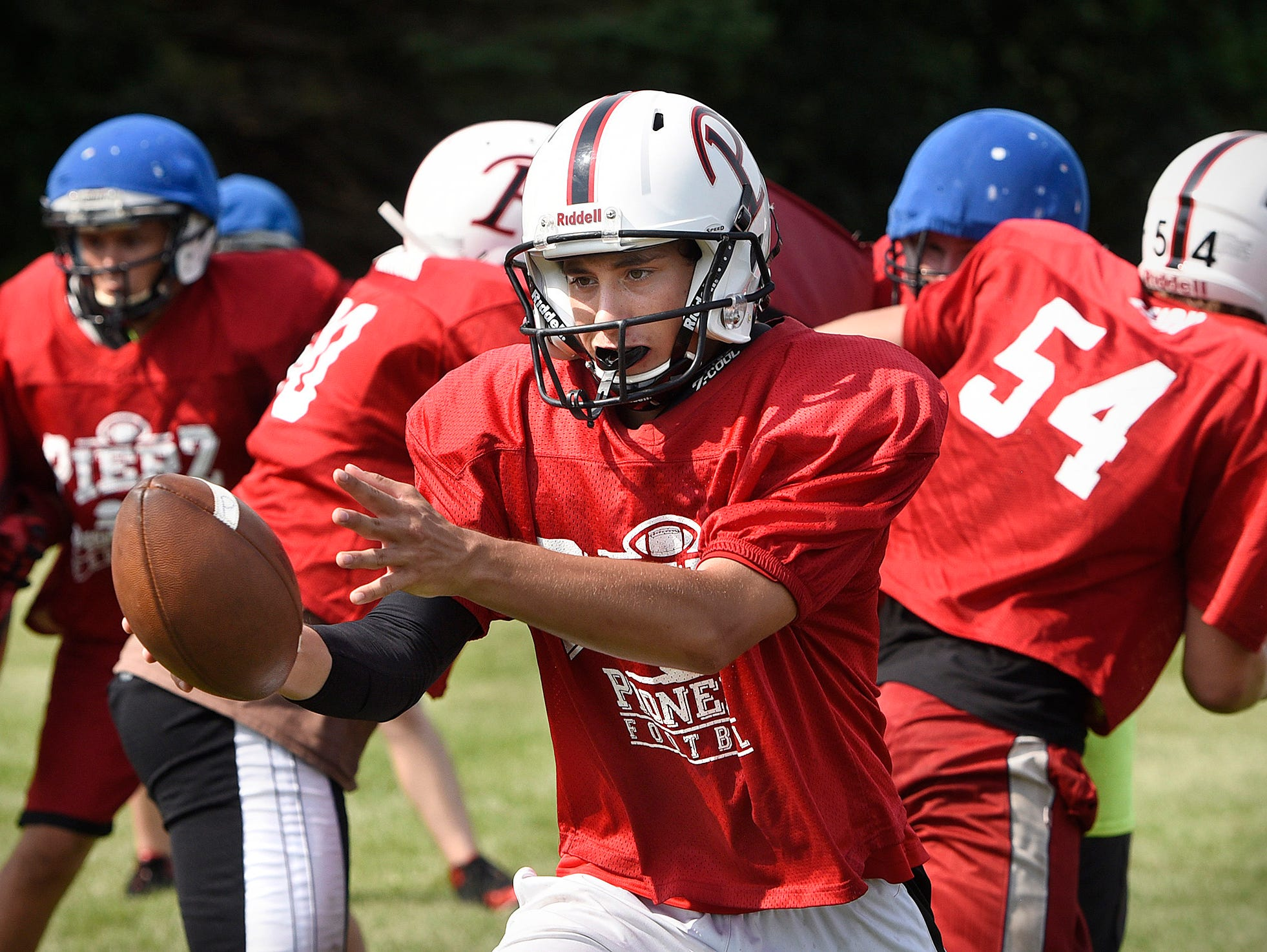 Aaron Weber turns to hand the ball off to a running back during practice for Pierz in the preseason. Weber sprained his ankle in the section championship game and did not play in the state quarterfinals.