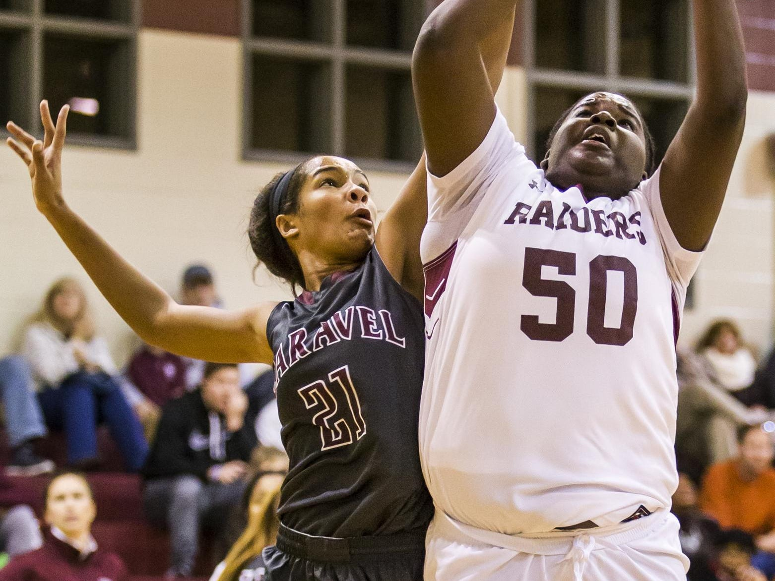 Concord's Breanna Grant (No. 50) is fouled by Caravel's Kaylee Otlowski (No. 21) as she puts up a shot in the first half of Caravel's 42-26 win over Concord at Concord High School on Monday night.