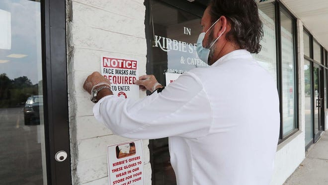 Owner Kris Burns places a sign Friday at the front of Kirbie's Meats & Catering in Stow requiring customers to wear masks because Summit County is under alert Level 3.