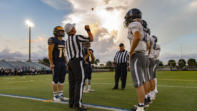 Officials, Dwyer players, right, and Boca Raton players gather for the pregame coin toss in a 2019 game. The fall high school sports season is in flux currently with coronavirus cases spiking in Florida, especially south Florida.