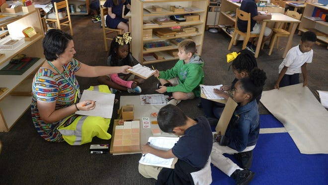 Alana Brown sits on the floor to work with a group of students at Coastal Empire Montessori Charter School.