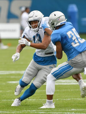 Lions wide receiver TJ Jones, left, and cornerback Jamal Agnew work during a drill at Wednesday's training camp practice.