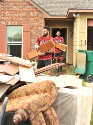 Ragin' Cajun quarterbacks Jordan Davis (front) and Anthony Jennings help demo a flooded home in Youngsville on Tuesday.