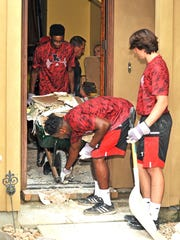 Ragin' Cajuns football players help demo a flooded