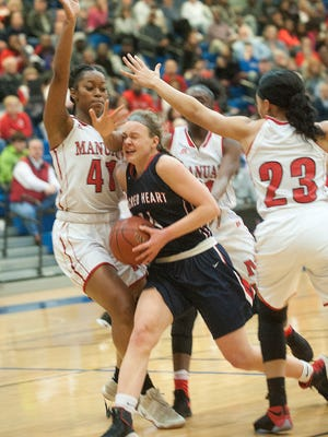 Sacred Heart guard Grace Berger collides with Manual forward-center Nila Blackford on the way to the basket. Manual guard Tonysha Curry, is at right. March 4, 2017