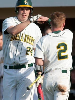 Floyd Central's Dalton Drexler, right, is congratulated by Floyd Central's Jon Cato after Drexler scores on a wild pitch by Jeffersonvillle starting pitcher Gabe Bierman.04 April 2017
