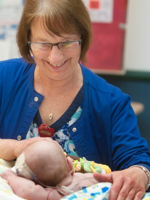 Registered Nurse Joanie Strotman is one of the longest tenured nurses at Norton Children's Hospital. Here, she tenderly attends to an infant patient in the Pediatric Intensive Care Unit of the hospital.