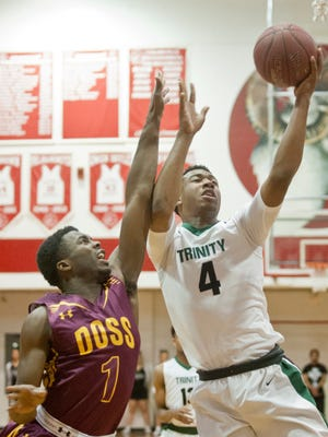 Trinity guard Jay Scrubb puts up a shot as Doss forward ShawnKel Knight-Goff comes down on his arm in the boys Louisville Invitational Tournament championship. Jan. 21, 2018