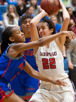 Mercer County forward Timberlynn Yeast, left, and Mercer County guard Toni McCombs pressure Sacred Heart center-forward Kristen Clemons as Clemons drives to the basket in the 46th annual Girls Louisville Invitational Tournament championship game. Clemons scored 16 points in the contest.Jan. 27, 2018