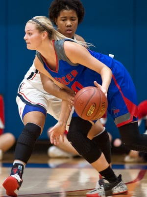 Mercer County guard Emma Davis drives around Sacred Heart guard Erin Toller in the 46th annual Girls Louisville Invitational Tournament championship game.