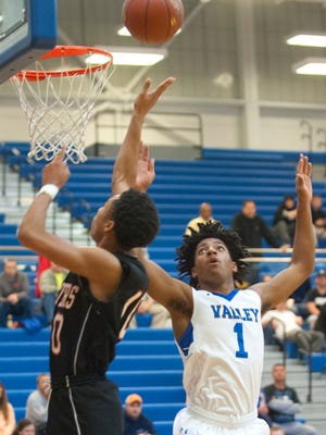 PRP guard Gerald Gray drives to the basket past Valley guard Cam Wilson in the 21st District tournament. Feb. 21, 2018