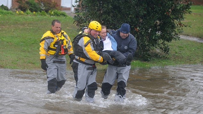 Emergency personnel evacuates a resident of the Somers Cove Apartments after Hurricane Sandy knocked out power and water to the town in 2012.