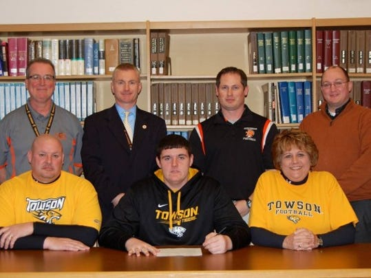 Pictured, from left, front row: Father Brian Kauffman, Matt Kauffman, mother Nora Kauffman. Back row, from left: Mark O'Reilly, assistant AD, Chris Adams, AD, Jeremy Jones, head coach, Brian Ellis, principal. (SUBMITTED)