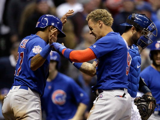 Chicago Cubs' Javier Baez, right, reacts after scoring with Addison Russell against the Milwaukee Brewers during the sixth inning of a baseball game Friday, April 6, 2018, in Milwaukee. (AP Photo/Jeffrey Phelps)