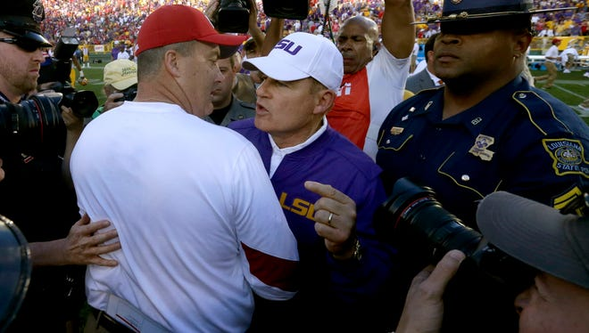 Wisconsin head coach Paul Chryst (left) greets LSU head coach Les Miles at midfield after the Badgers' 16-14 victory in the Lambeau College Classic on Saturday at Lambeau Field in Green Bay. Wisconsin beat LSU 16-14.