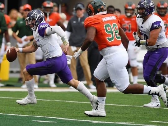 ACU quarterback Dallas Sealey, left, carries the ball