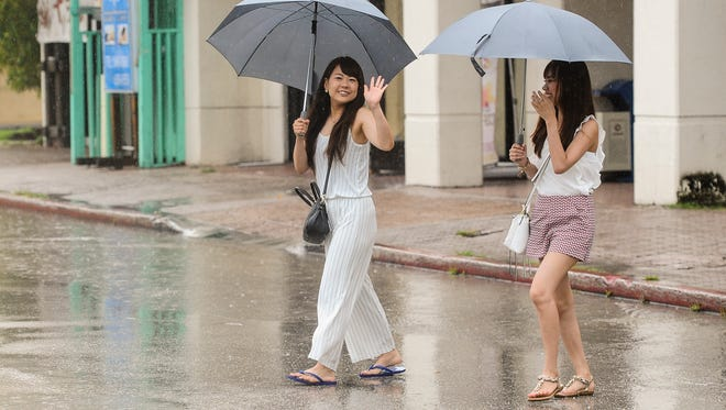 Tourists make the best of their stay on Guam despite the inclement weather experienced in Tumon on Aug. 3.