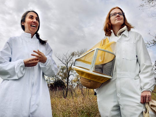 Beekeepers and friends Erin Gutwasser, left, and Amanda Loewen talk Sunday after checking on their hives.
