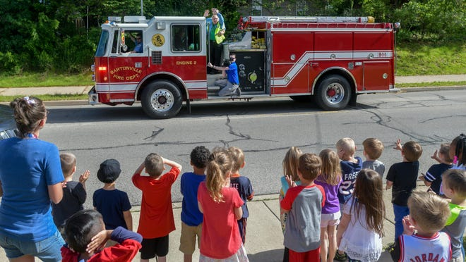 Gerald Beckette, 85, in yellow vest, waves from atop a Bartonville Fire Department fire truck in May 2019 as the village honored the retiring crossing guard and custodian with a parade and proclamation for his 67 years of service in the Oak Grove school district.