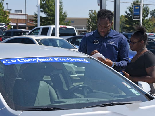 Terrance Cooper, a salesman at Chevyland, assists Damaia Burks look at a pre-owned vehicle on the Shreveport dealers lot.