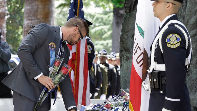 Zack Zerebny touches the name of his wife, slain Palm Springs police officer Lesley Zerebny, during the Peace Officers Memorial, May 8, 2017, in Sacramento.
