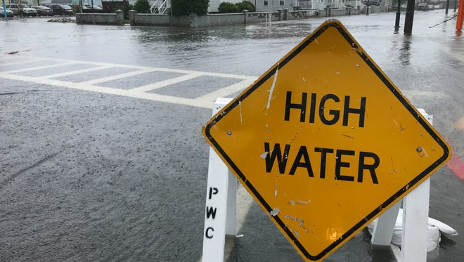 A high water sign has been placed along St. Louis Ave. in Ocean City, Md. where road are under water due to heavy rains on Friday, May 18, 2018.